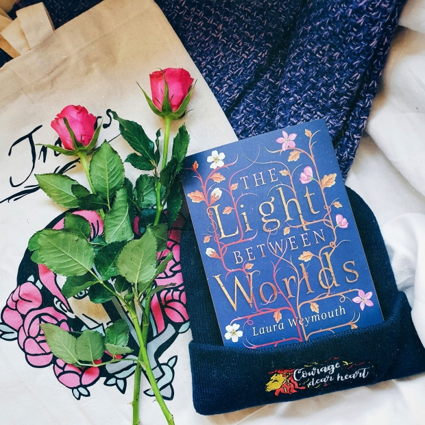 The Light Between Worlds book on top of the ADSOM tote with some pink roses